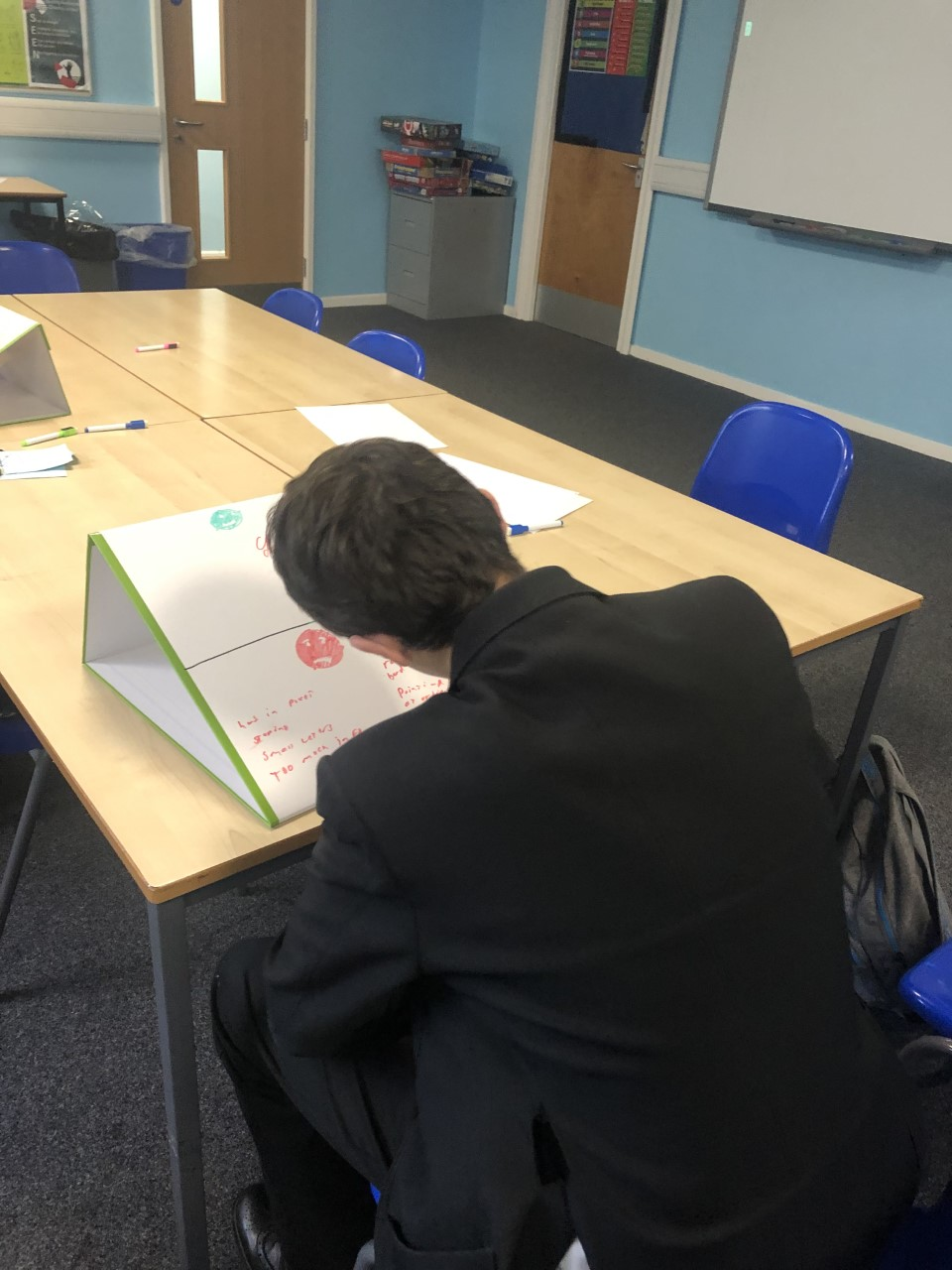 Special Educational Needs Department uses school tabletop whiteboards as a writing slope in lessons
